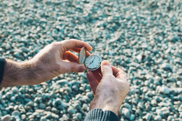 Orologio da taschino nelle mani degli uomini. pelle di vitiligine. orario terrestre. sfondo di ciottoli