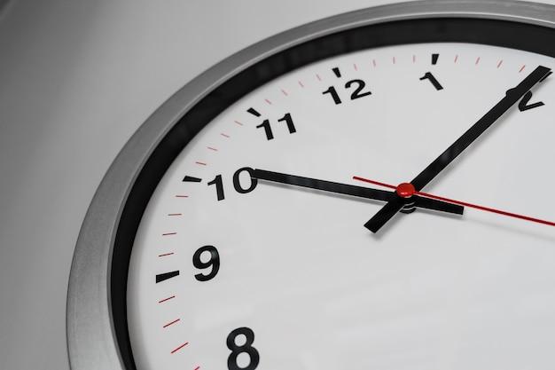 Orologio del primo piano sulla parete per l'orario di ufficio in tempo concetto.