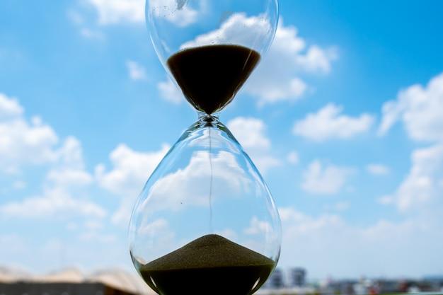 Orologio della sabbia con il concetto di affari della nuvola e del cielo