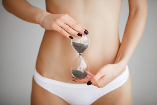 Orologio della sabbia della tenuta della donna sopra il suo stomaco. concetto di educazione sessuale igiene della salute