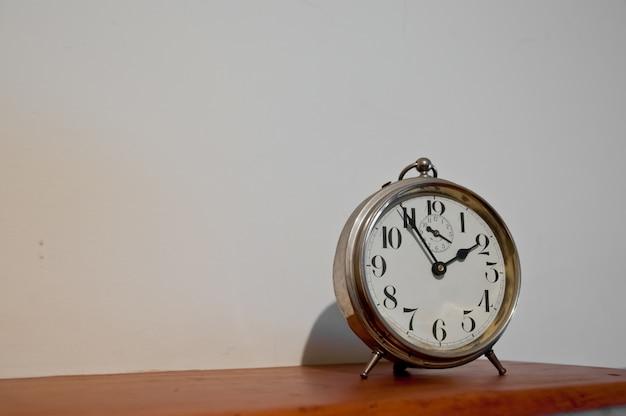 Orologio dorato d'annata classico su una tavola con copyspace