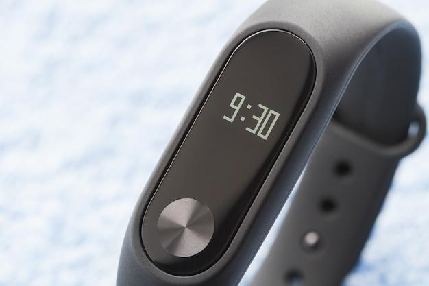 Orologio fitness nero (tracker attività) sulla superficie tessile blu. primo piano, messa a fuoco selettiva