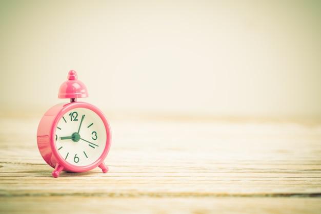Orologio rosa sul tavolo in legno