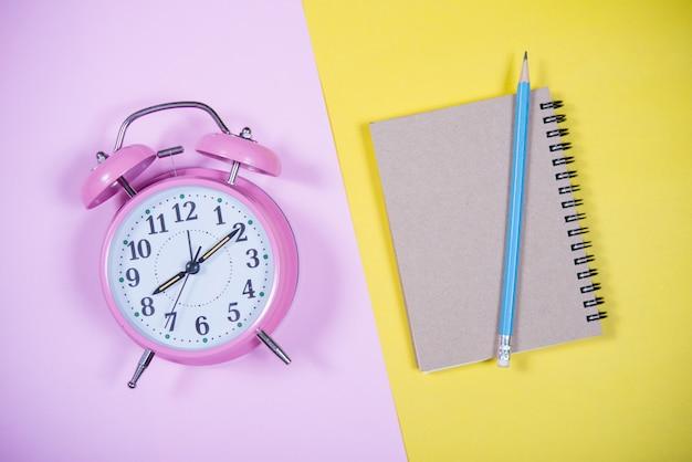 Orologio rosa sullo sfondo colorato, concetto di educazione