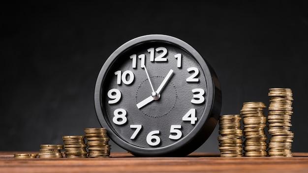 Orologio rotondo tra le monete in aumento sullo scrittorio di legno contro il contesto nero