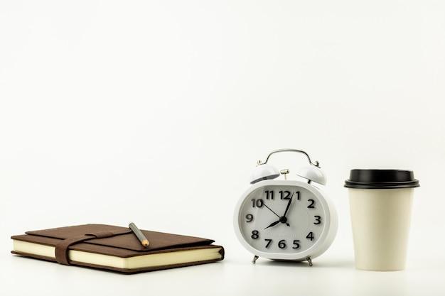 Orologio, tazza di caffè, matita e un taccuino di cuoio sul fondo bianco dello scrittorio con lo spazio della copia. - forniture per ufficio o concetto di educazione.