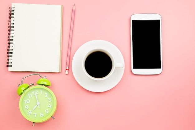 Orologio verde del caffè nero del telefono cellulare del taccuino su fondo rosa