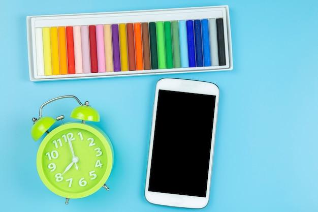 Orologio verde pastello e cellulare su sfondo blu stile pastello