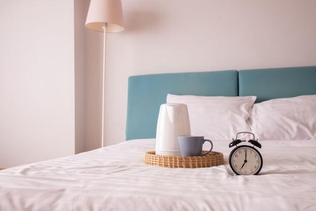Orologio vintage e bevanda calda di caffè sul letto.