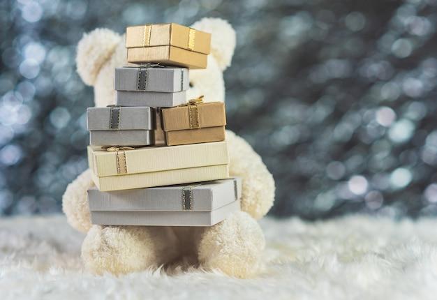 Orsacchiotto bianco che tiene i contenitori di regalo su lana