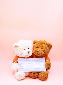 Orsacchiotto bianco e marrone si stringono insieme per tenere una maschera per proteggere da coronavirus e polvere di pm2.5. concetto di igiene e sanità