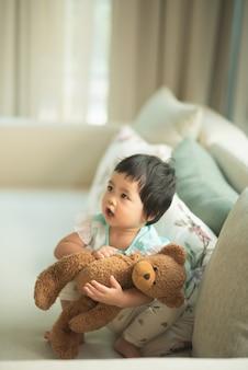 Orsacchiotto che abbraccia bambino sveglio rilassarsi sul divano in bagno