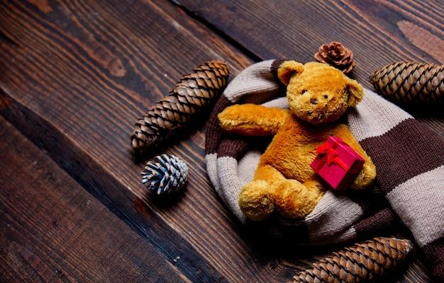 Orsacchiotto con scatola gfit e sciarpa sul tavolo di legno