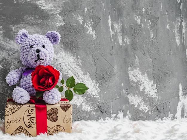 Orsacchiotto con una rosa rossa su una confezione regalo