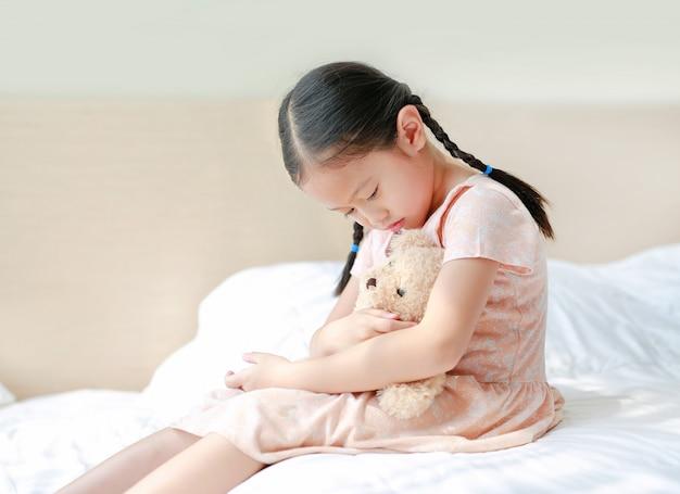 Orsacchiotto d'abbraccio asiatico pacifico della bambina mentre sedendosi sul letto a casa