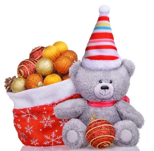 Orsacchiotto divertente in cappello con la borsa del babbo natale piena di giocattoli
