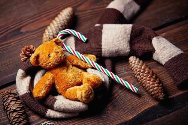 Orsacchiotto e bastoncino di zucchero con la sciarpa sulla tavola di legno