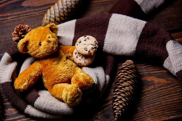 Orsacchiotto e biscotti con la sciarpa sulla tavola di legno
