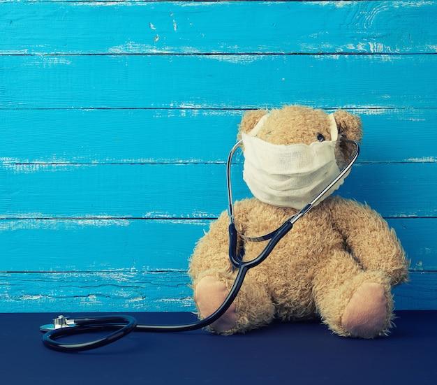 Orsacchiotto è seduto in una maschera medica bianca con stetoscopio nero appeso al collo