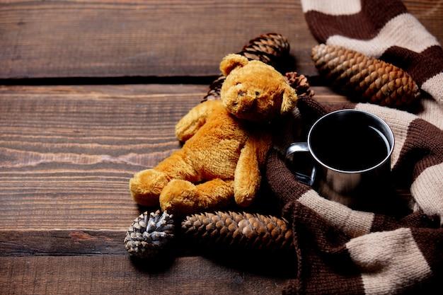 Orsacchiotto e tazza di caffè con la sciarpa sulla tavola di legno