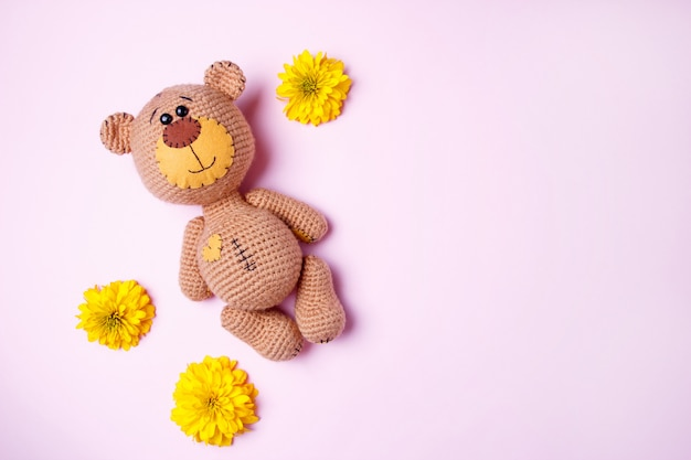 Orsacchiotto fatto a mano di amigurumi con il crisantemo giallo isolato su un fondo rosa. sfondo bambino. copia spazio, vista dall'alto.