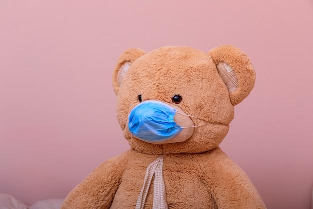 Orsacchiotto in una mascherina medica su una priorità bassa bianca. medicina respiratoria coronavirus o concetto covid 19.
