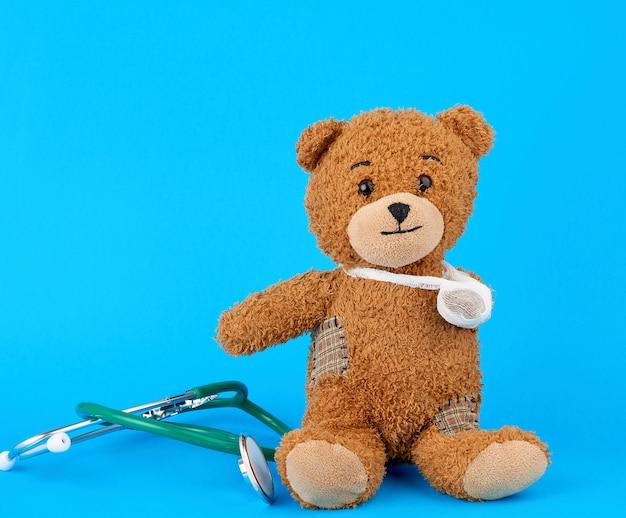 Orsacchiotto marrone con una zampa bendata seduto su uno sfondo blu