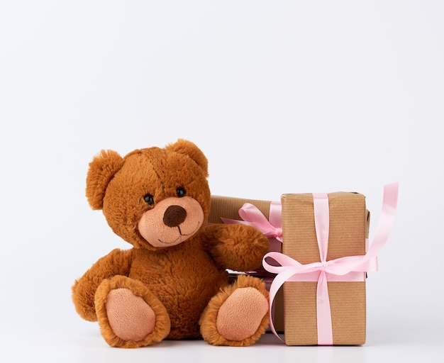 Orsacchiotto marrone, pila di regali in scatole avvolte in carta marrone
