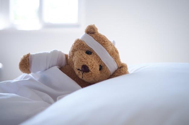 Orsacchiotto sdraiato a letto con una fascia e un panno coperto