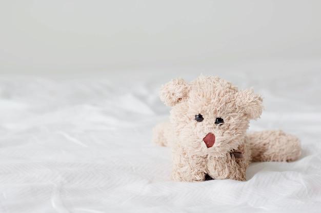 Orsacchiotto sdraiato rilassante sul letto