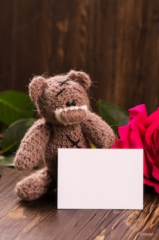 Orsetto con una bellissima rosa rosa.