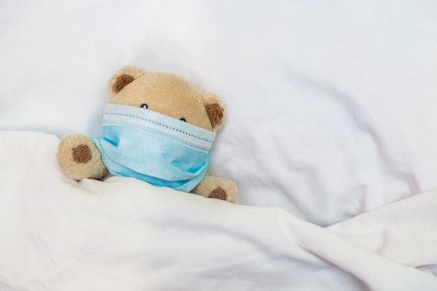 Orsetto giocattolo giace a letto. coronovirus, quarantena, epidemia, pandemia, influenza, raffreddore, malattia. concetto di medicina e salute.