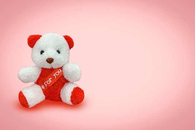 Orso bambola seduta con sfondo rosa,