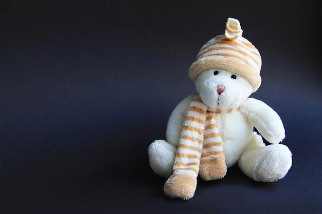 Orso bianco giocattolo in cappello e sciarpa su sfondo nero