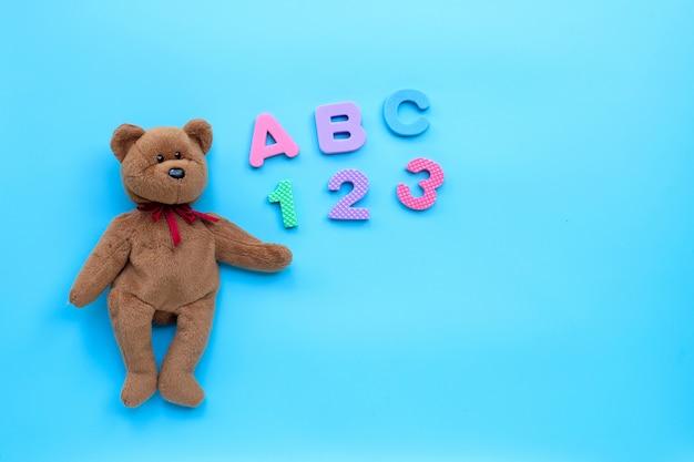 Orso bruno giocattolo con alfabeto inglese e numeri su sfondo blu. concetto di educazione