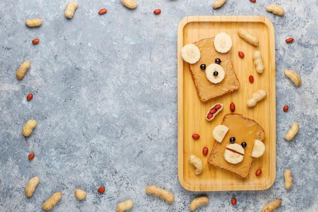 Orso divertente e scimmia faccia sandwich con burro di arachidi, banana e ribes nero, arachidi, vista dall'alto