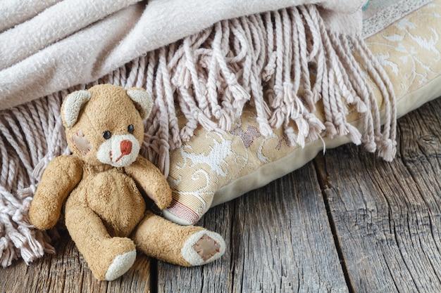 Orso e plaid svegli del giocattolo sulla tavola