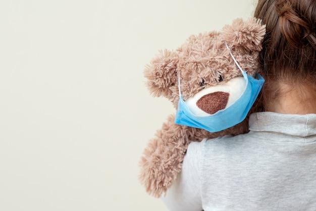 Orso giocattolo con maschera protettiva sulla spalla del bambino.