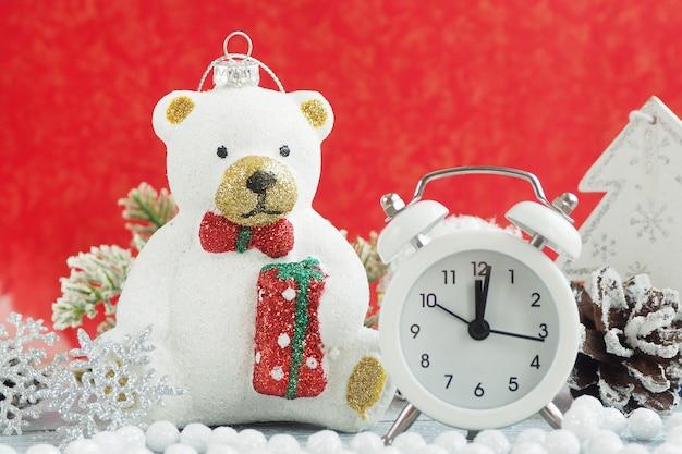Orso polare giocattolo di natale, sveglia, fiocco di neve d'argento, pigna e perline bianche. sfondo rosso