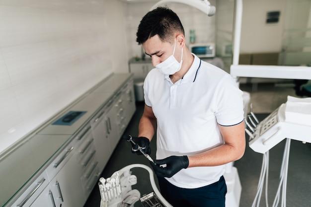 Ortodontista che controlla attrezzatura chirurgica