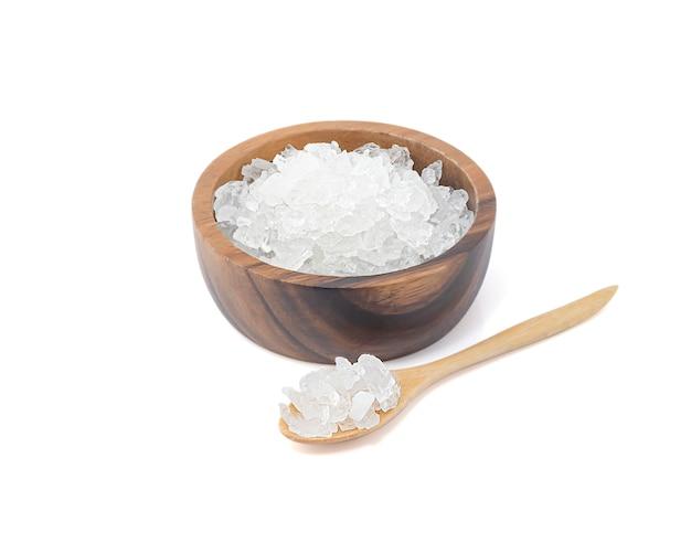 Oscilli lo zucchero in ciotola di woodden e cucchiaio di woodden isolati sulla parete bianca