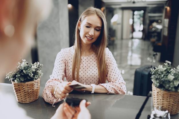 Ospite dell'hotel giovane bella donna che paga per il suo soggiorno con carta di credito alla reception