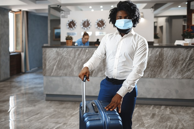 Ospite dell'hotel uomo africano con valigia che indossa una maschera protettiva per proteggersi dal coronavirus