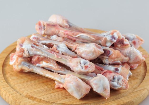 Ossa di pollo grezze su bianco