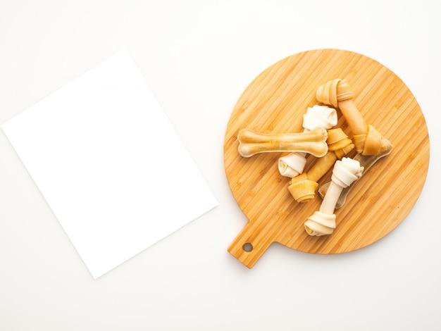 Osso del cibo per cani sul legno a pezzi di taglio su bianco