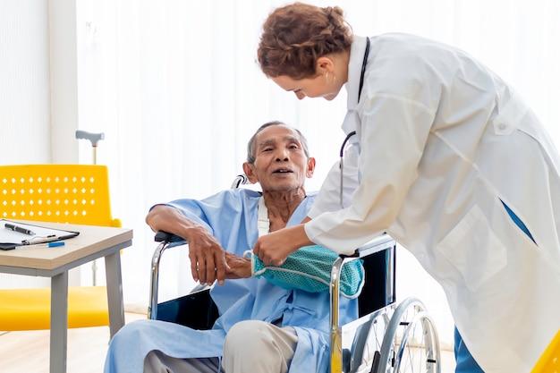 Osso di braccio rotto controllo professionale caucasico di medico della donna in colata con il paziente dell'uomo senior nella stanza di ospedale.