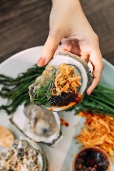 Ostrica fresca con guscio in mano che condimento con scalogno fritto, pasta di peperoncino, acacia pennata e salsa di frutti di mare in stile tailandese.