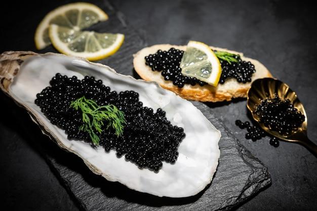 Ostriche aperte con caviale nero di storione e limone su ghiaccio sul tavolo di cemento nero. vista dall'alto, disteso, copia spazio.
