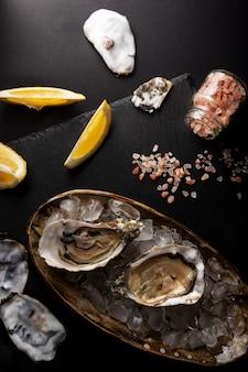 Ostriche aperte sul piatto con limone e sale rosa