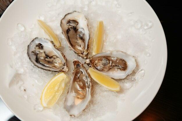 Ostriche appena aperte su un piatto con ghiaccio, fette di limone, rametti di menta e rosmarino su uno spazio di pietra scura. posto per il testo, vista dall'alto. cena romantica in un ristorante.